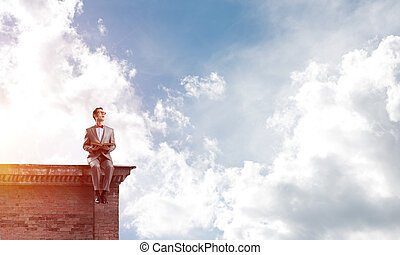 Young businessman or student studying the science on building roof