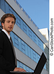 Young businessman outside a modern office building