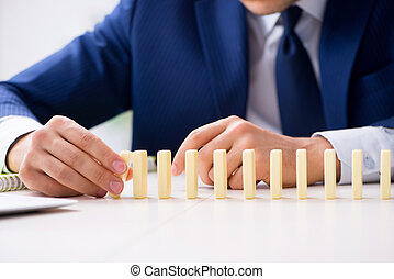 Young businessman playing with domino in office