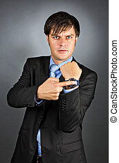 Young businessman pointing to his watch with an angry expression on his face isolated on gray background