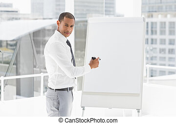 Young businessman presenting at whiteboard with marker