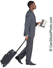 Young businessman pulling his suitcase