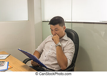 Young businessman reading financial document in the meeting room