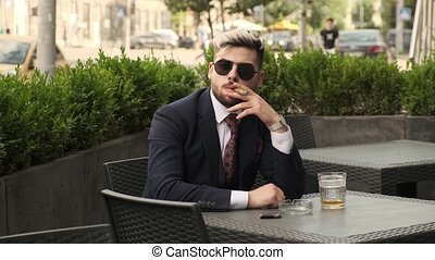 Young businessman relaxing and drinking coffee sitting in cafe on the terrace in the city