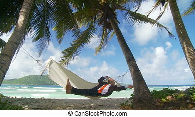young businessman relaxing in hammock