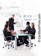Young businessman reporting to sales to his team in an...