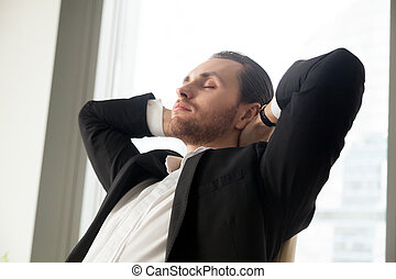 Young businessman resting at work with his hands behind head.