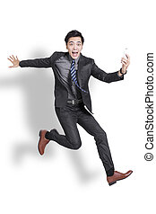 Young businessman runnung fast and holding mobile.