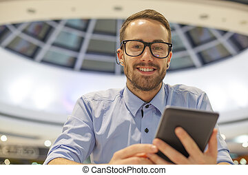 Young Businessman seating on table in restoran and use mobile de