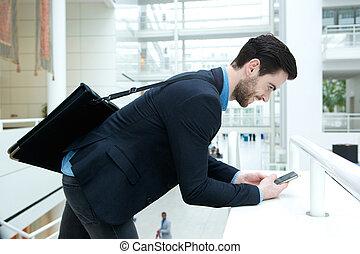 Young businessman sending text message