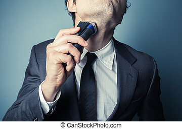 Young businessman shaving - A young businessman is shaving...
