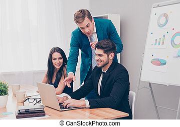 Young businessman showing financial plan on laptop to his colleagues