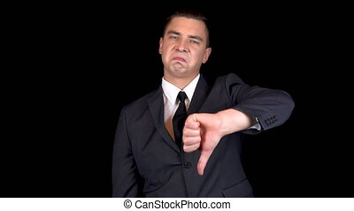 Young businessman shows dislike on hand. Man in a black suit on a black background