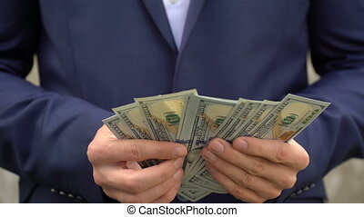Young businessman shows his money close-up. - Young...