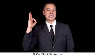 Young businessman shows ok sign on his hand. Man in a black suit on a black background