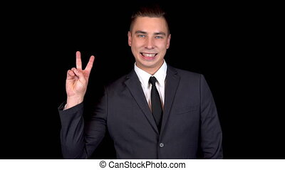 Young businessman shows victory sign with his hand. Man in a black suit on a black background