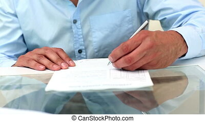 Young businessman signing a contract in office
