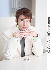 Young businessman sits at office on workplace