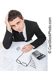 young businessman sitting and working with documents. upset...
