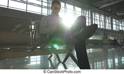 Young businessman sitting at airport and using smartphone with sun flare at background. Close up portrait of handsome business man in sunglasses with smart phone at the terminal. Slow motion