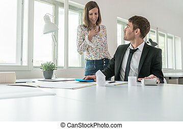 Young businessman sitting at his office desk reviewing financial report