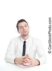 Young Businessman sitting at the desk with serious face