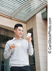 Young businessman sitting in a cafe on a coffee break.