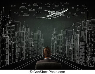 Young businessman sitting in an office chair and looking on a sketched cityscape drawing on a chalkboard