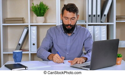 young businessman sitting in modern office - worker writing...