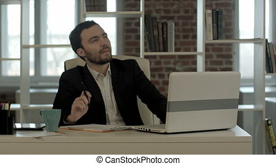 Young businessman sitting in office, search idea