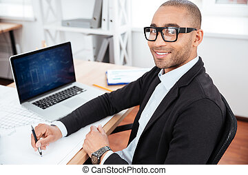 Young businessman sitting in the office and looking at camera
