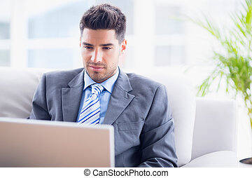 Young businessman sitting on couch using his laptop