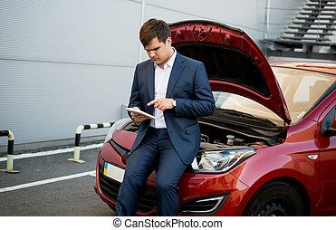 businessman sitting on hood of broken car and searching how to f
