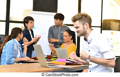 Young businessman smiling at a laptop computer in the office