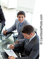 Young businessman smiling at the camera in a meeting