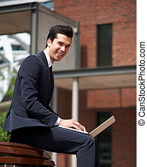 Young businessman smiling outdoors with laptop