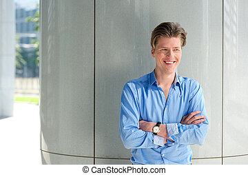 Young businessman smiling with arms