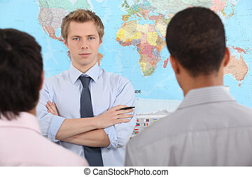 Young businessman speaking in front of a world map