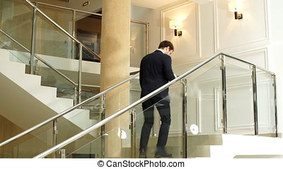 Young businessman speaking on the phone while walking.