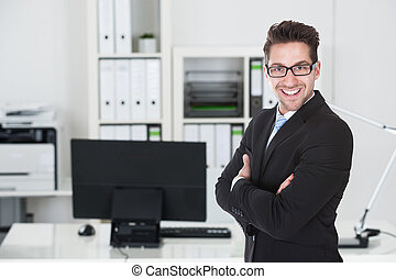 Young Businessman Standing Arms Crossed In Office