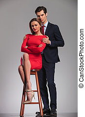 businessman standing behind woman in red dress sitting on chair