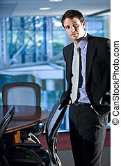 Young businessman standing in boardroom