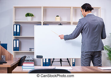 Young businessman standing in front of white board