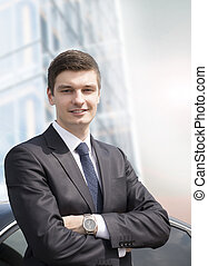 Young businessman standing near his car