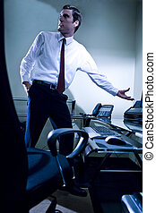 Young businessman standing next to desk pointing at computer screen