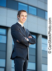Young businessman standing outdoors smiling