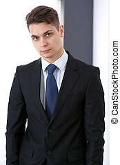 Young businessman standing straight in office. Business concept