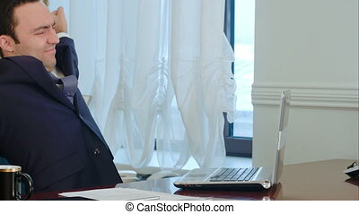 Young businessman stretching his arms in office and start working on laptop