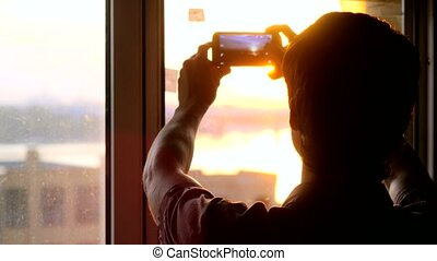 Young businessman taking picture with mobile phone against...