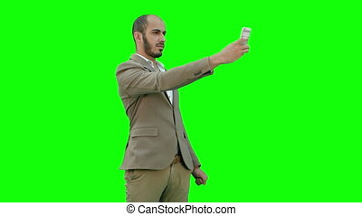 Young businessman taking selfies on phone on a Green Screen, Chroma Key.
